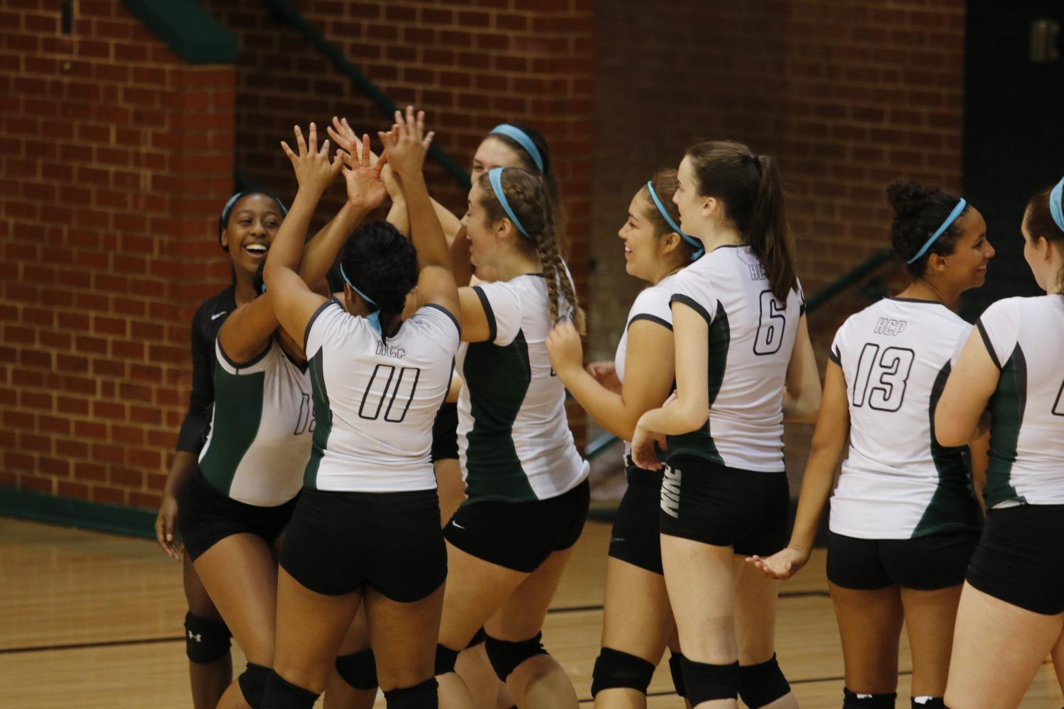 Volleyball+team+comes+together+to+high+five+each+other+after+a+play.+