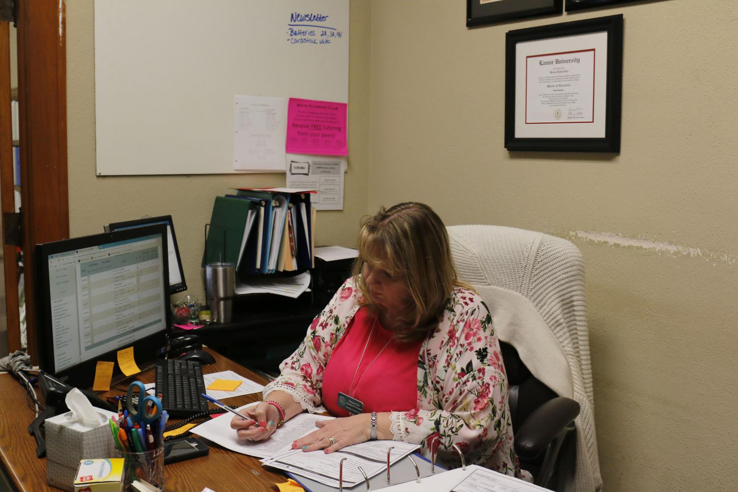 Mrs. Cox works at her desk